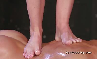 Blonde masseuse gives massage with feet